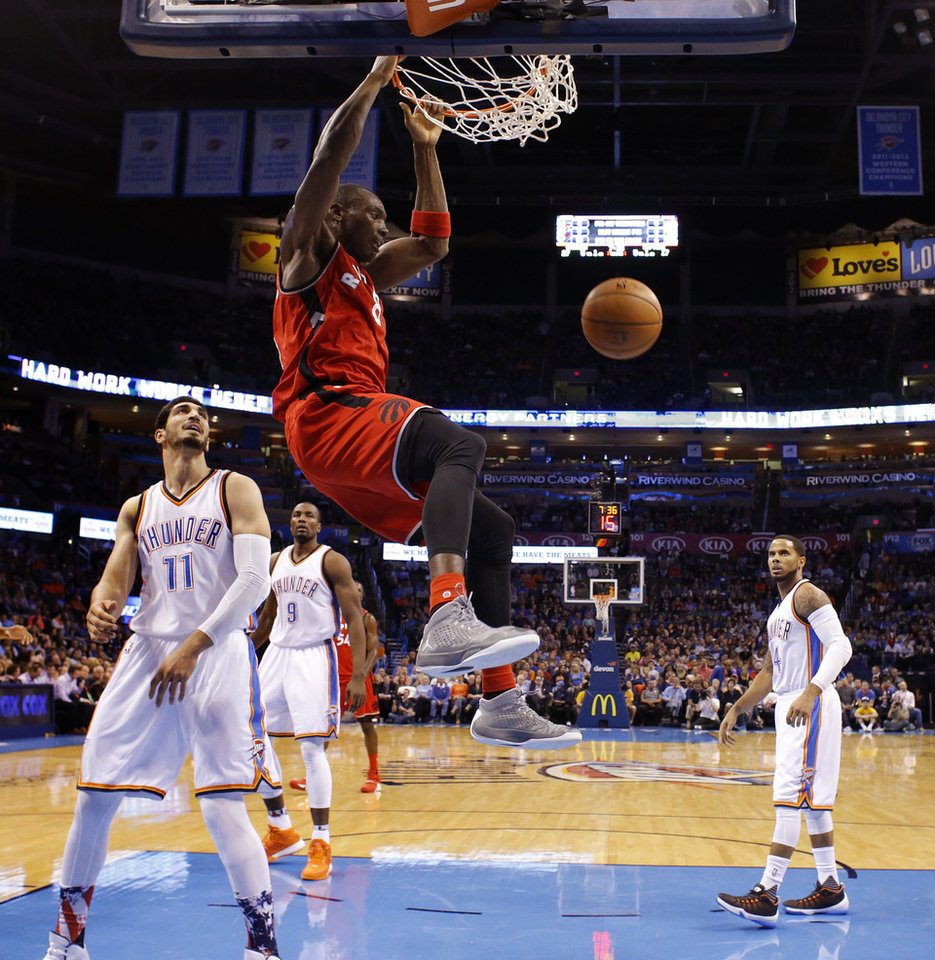 Photo - Toronto's Bismack Biyombo (8) dunks the ball as Oklahoma City's Enes Kanter (11), Serge Ibaka (9) and D.J. Augustin (14) watch during an NBA basketball game between the Oklahoma City Thunder and the Toronto Raptors at Chesapeake Energy Arena on Wednesday, Nov. 4, 2015. The Thunder lost 103-98. Photo by Bryan Terry, The Oklahoman
