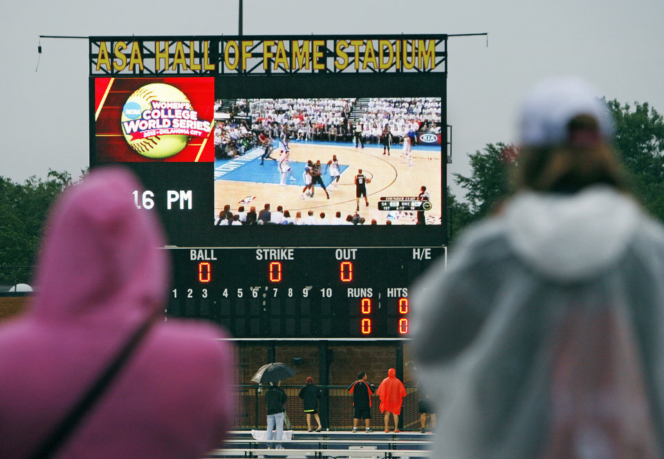 Photo - Softball fans watch Game 6 of the NBA Western Conference Finals between the Oklahoma City Thunder and the San Antonio Spurs on the scoreboard during a rain delay at  Game 3 of the Women's College World Series softball championship between OU and Alabama at ASA Hall of Fame Stadium in Oklahoma City, Wednesday, June 6, 2012.  Photo by Nate Billings, The Oklahoman