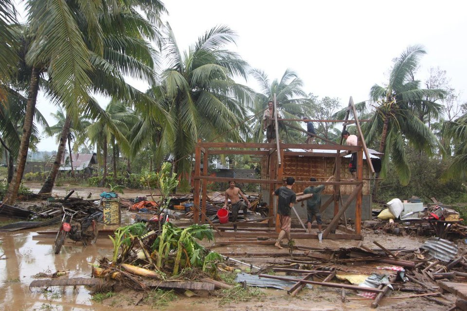 Photo - Residents repair their damaged homes after Typhoon Bopha made landfall in Compostela Valley in southeastern Philippines Tuesday Dec. 4, 2012. Typhoon Bopha (local name Pablo), one of the strongest typhoons to hit the Philippines this year, barreled across the country's south on Tuesday, killing at least 40 people and forcing more than 50,000 to flee from inundated villages.  (AP Photo/Karlos Manlupig)