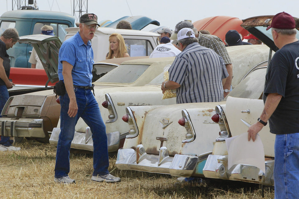 Photo - Car buffs look over Chevrolet vehicles during a preview for an auction of vintage cars and trucks from the former Lambrecht Chevrolet dealership in Pierce, Neb., Friday Sept. 27, 2013. The auction takes place on Saturday and Sunday. (AP Photo/Nati Harnik)