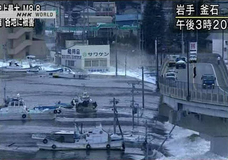 Photo - In this video image taken from Japan's NHK TV,  a wave from the tsunami sweeps boats inland in Kamaishi, Iwate Prefecture, Japan Friday March 11, 2011 following a massive earth quake. A magnitude 8.9 earthquake slammed Japan's northeastern coast Friday, unleashing a 13-foot (4-meter) tsunami that swept boats, cars, buildings and tons of debris miles inland. Fires triggered by the quake burned out of control up and down the coast.  (AP PHOTO/NHK TV) MANDATORY CREDIT, JAPAN OUT, TV OUT,  NO SALES, EDITORIAL USE ONLY ORG XMIT: LON827