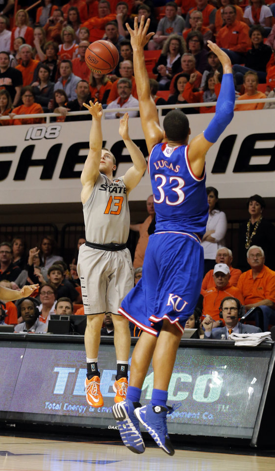 Photo - Oklahoma State's Phil Forte III (13) shoots over Kansas's Landen Lucas (33) during the men's college basketball game between Oklahoma State University and the University of Kansas at Gallagher-Iba Arena in Stillwater, Okla.,  Saturday, Feb. 7, 2015. OSU won 67-62. Photo by Sarah Phipps, The Oklahoman