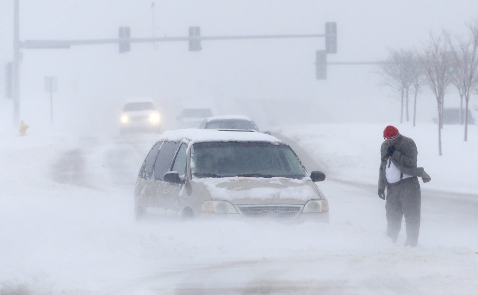 Photo - A man waits for help after becoming stuck in snow along West 6th Street in Lawrence, Kan., Sunday, March 24, 2013. Few signs of spring are being found in parts of the Midwest as a snowstorm brings heavy snow and high winds. (AP Photo/Orlin Wagner)
