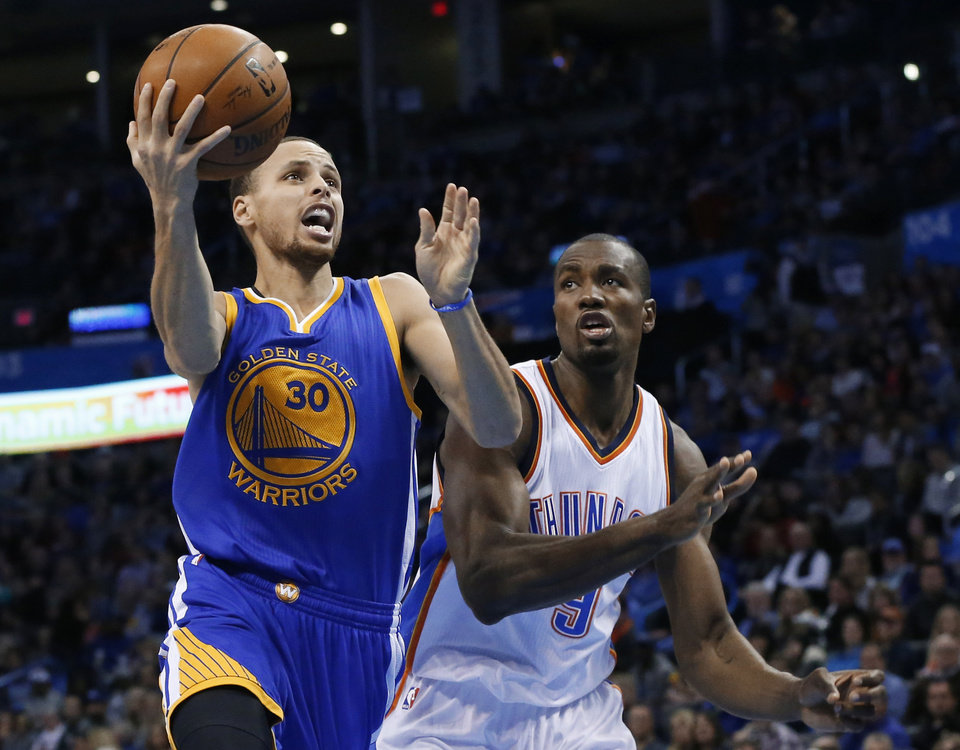 Photo - Golden State Warriors guard Stephen Curry (30) goes in for a shot in front of Oklahoma City Thunder forward Serge Ibaka (9) during the second quarter of an NBA basketball game in Oklahoma City, Friday, Jan. 16, 2015. (AP Photo/Sue Ogrocki)