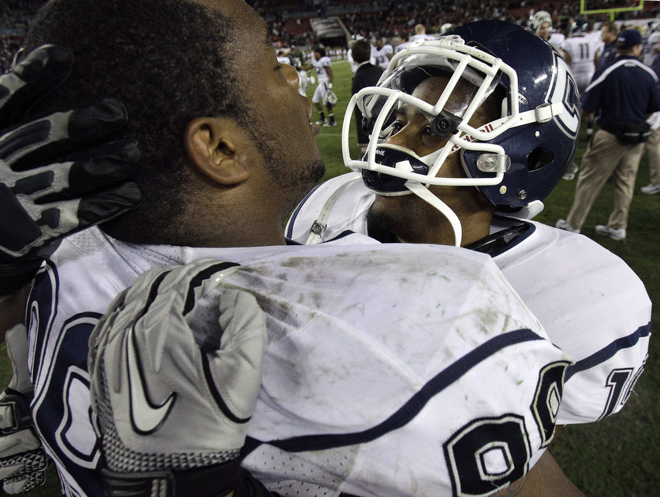 Connecticut defensive tackle Kendall Reyes (99) celebrates with Kijuan Dabney (19) after the team defeated South Florida 19-16 to win the Big East conference title during an NCAA college football game Saturday, Dec. 4, 2010, in Tampa, Fla. AP Photo/Chris O'Meara