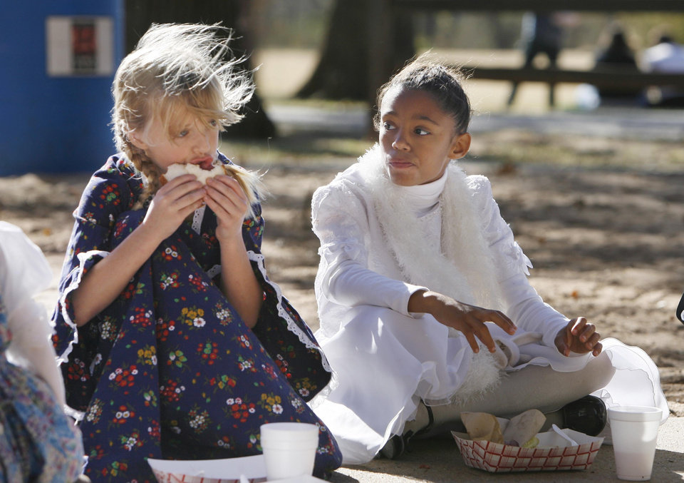 Photo - 9-year-olds Clara O'Connor (left) from Clegern School in Edmond and Jennifer Jenkins from Fogarty Elementary School in Guthrie, enjoy free brisket sandwiches at Mineral Wells Park, during the Centennial Day celebrations in Guthrie, OK, Thursday, Nov. 16, 2007. By Paul Hellstern / The Oklahoman