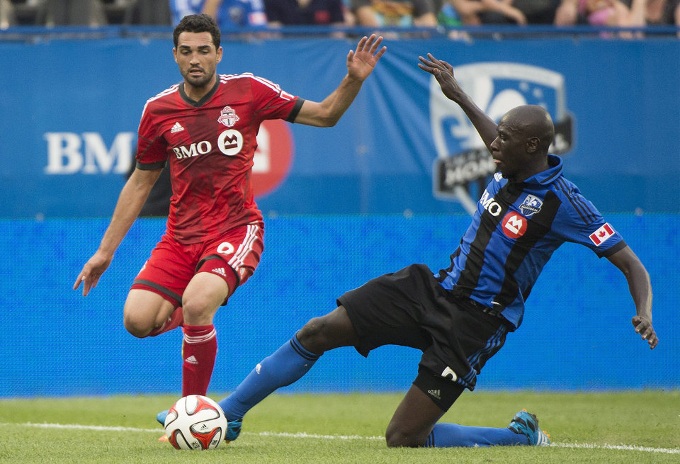 Photo - Montreal Impact's Hassoun Camara, right, slides in on Toronto FC's Gilberto during the second half of a soccer match in Montreal, Saturday, Aug. 2, 2014. (AP Photo/The Canadian Press, Graham Hughes)
