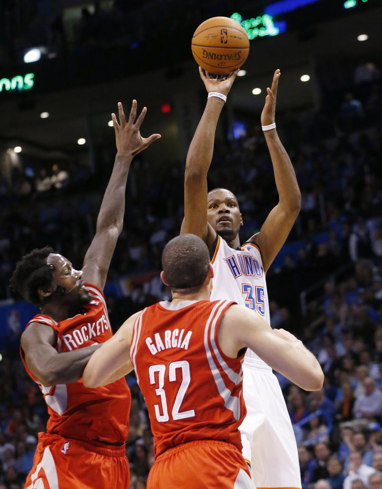 Photo - Oklahoma City Thunder forward Kevin Durant (35) shoots over Houston Rockets guard Pat Beverley (2) and guard Francisco Garcia (32) during the fourth quarter of an NBA basketball game in Oklahoma City, Tuesday, March 11, 2014. Durant scored 42 points as Oklahoma City won 106-98. (AP Photo/Sue Ogrocki)