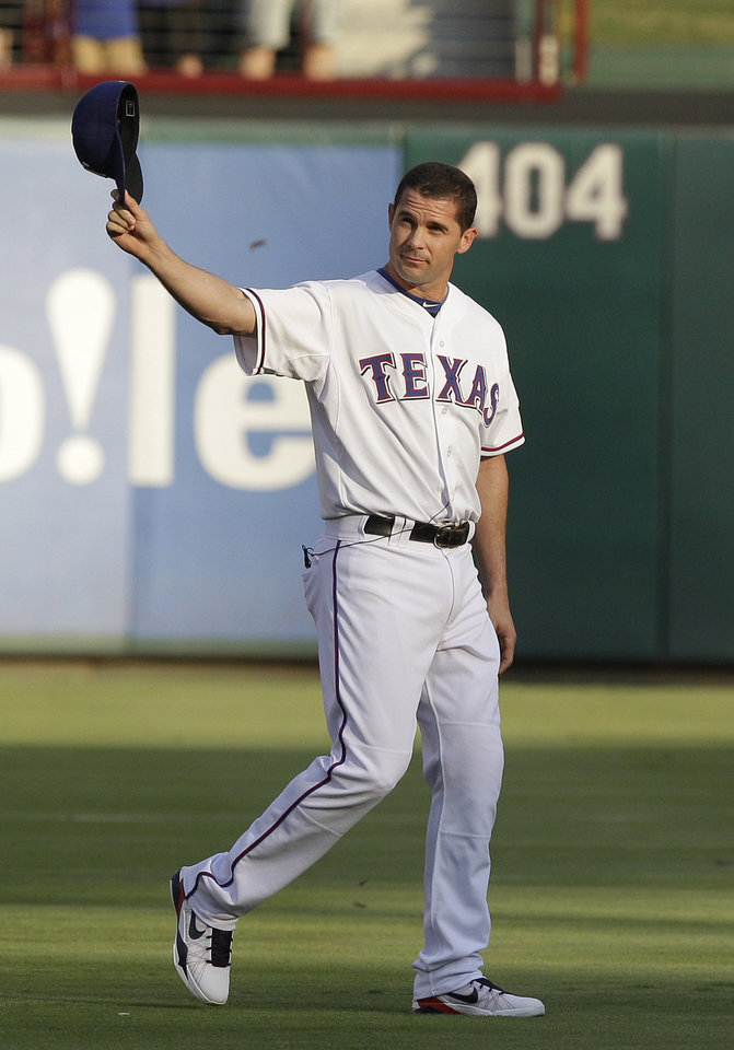 Photo - FILE - In this Aug. 11, 2012, file photo, Texas Rangers Michael Young waves to fans before a baseball game in Arlington, Texas. Young is retiring after a 13-year major league career, nearly all of it with the Rangers.  The seven-time All-Star retires with a .300 career average and as Texas' hits leader with 2,230. He was the 2008 AL Gold Glove at shortstop. (AP Photo/LM Otero, File)