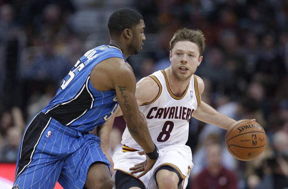 Photo - Cleveland Cavaliers' Matthew Dellavedova (8), from Australia, drives past Orlando Magic's E'Twaun Moore during the second quarter of an NBA basketball game Wednesday, Feb. 19, 2014, in Cleveland. Cleveland defeated Orlando 101-93. (AP Photo/Tony Dejak)