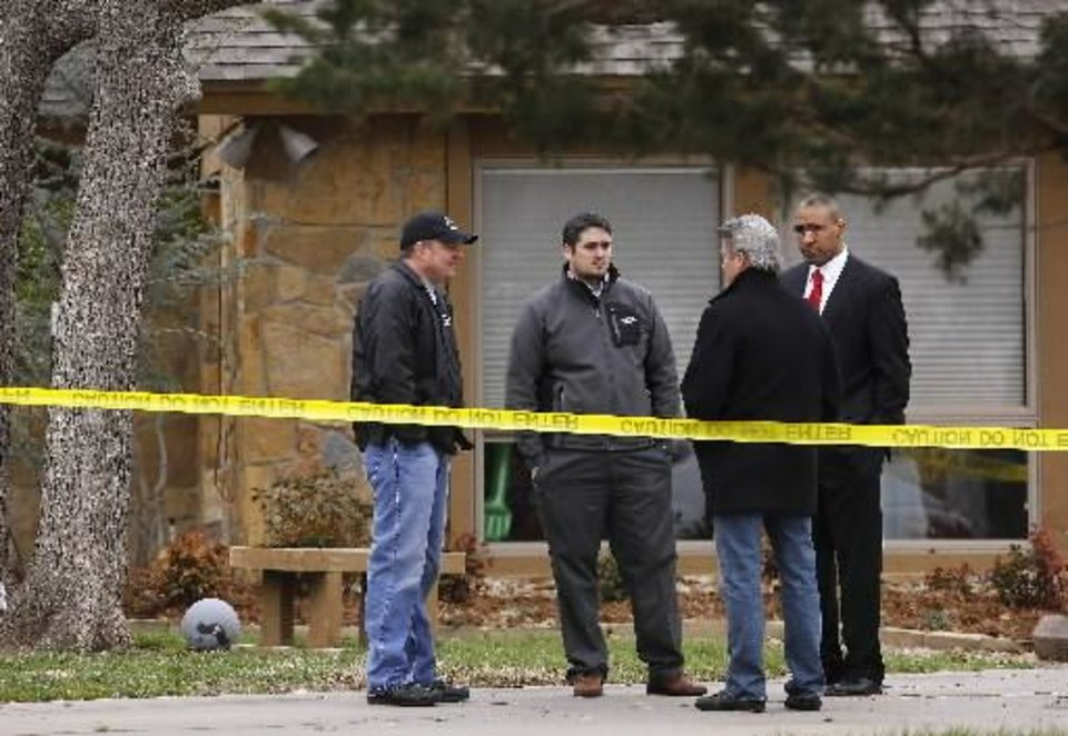 Photo - Pottawatomie County District Attorney Richard Smothermon, second from right, talks to other members of his staff in the driveway of the crime scene. Shawnee police investigate the scene of a pre-dawn homicide in an upscale neighborhood in northeast Shawnee Thursday, March 21, 2013. Police confirmed that Cathy Byus was killed in a domestic-related homicide inside her home at 27 Bella Vista Vista Lane. Photo by Jim Beckel