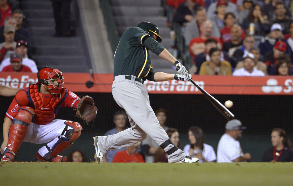 Photo - Oakland Athletics' Brandon Moss, right, hits a three-run home run as Los Angeles Angels catcher Chris Iannetta watches during the fourth inning of a baseball game, Wednesday, April 16, 2014, in Anaheim, Calif. (AP Photo/Mark J. Terrill)
