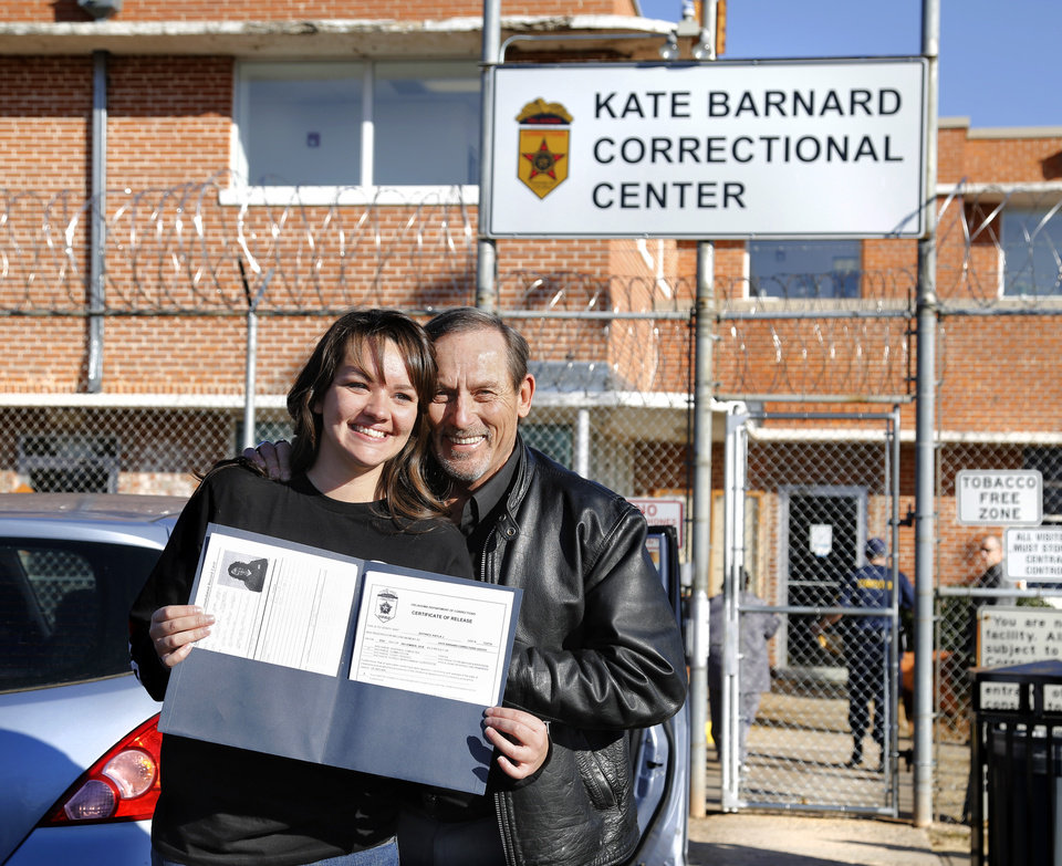 Photo - Kayla Jeffries shows her Department of Corrections folder while smiling and posing for a photo with her dad, Roy Jeffries, moments after walking through the 10-foot high security fence after being released from prison. Kayla Jeffries traded her orange prison uniform for freedom as she walked out of the Kate Barnard Correctional Center accompanied not by guards, but alongside her dad, stepmother and older sister Wednesday afternoon, Dec. 5, 2018. Earlier in the day, Gov. Mary Fallin commuted her 20-year prison sentence. The 26-year-old mother of two from Grove, Okla., was one of 21 Oklahoma inmates who had their sentences commuted to time served.  Inmates granted commutations were serving sentences 10 years or longer for drug possession and other crimes that now carry lesser punishments following recent reforms approved by voters and state lawmakers. The inmates were assisted through a commutation campaign led by Oklahomans for Criminal Justice Reform.  Photo by Jim Beckel, The Oklahoman.