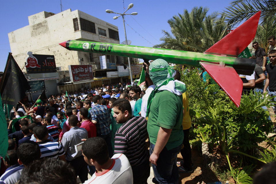 Photo - A supporter of Hamas holds a representation of a rocket as others shout slogans against the Israeli attack on the Gaza Strip, during a protest in the West Bank town of Tulkarem town on Friday, Aug. 1, 2014. A Palestinian man was shot and killed during clashes with Israeli troops near Tulkarem, Palestinian security sources said. (AP Photo/Mohammed Ballas)
