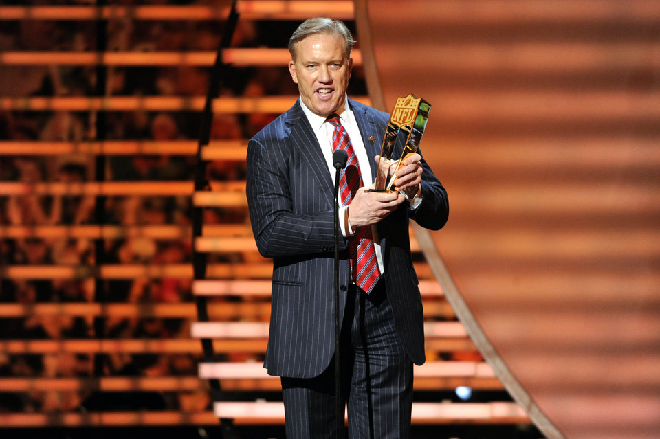 Photo - Former NFL quarterback John Elway accepts the award for AP Offensive Player of the Year on behalf of winner Peyton Manning of the Denver Broncos, at the third annual NFL Honors at Radio City Music Hall on Saturday, Feb. 1, 2014, in New York. (Photo by Evan Agostini/Invision for NFL/AP Images)