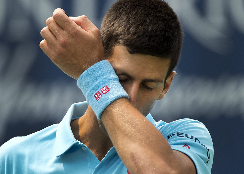 Photo - Novak Djokovic, of Serbia, wipes his face while playing against Jo-Wilfried Tsonga, of France, in a men's third round match at the Rogers Cup tennis tournament action in Toronto Thursday, Aug. 7, 2014. (AP Photo/The Canadian Press, Nathan Denette)