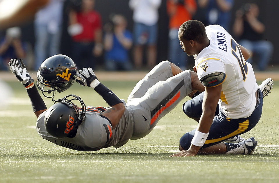 Photo - Oklahoma State's Lyndell Johnson (27) catches the helmet of West Virginia's Geno Smith (12) during a college football game between Oklahoma State University (OSU) and the West Virginia University at Boone Pickens Stadium in Stillwater, Okla., Saturday, Nov. 10, 2012. Photo by Sarah Phipps, The Oklahoman