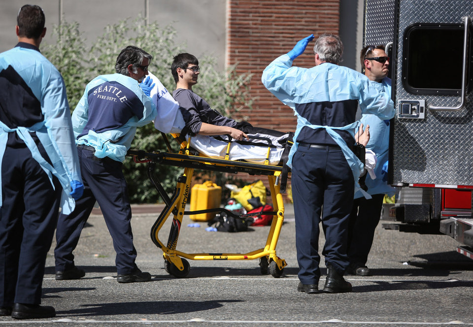 Photo - Jon Meis is taken from the scene by medics after a shooting at Seattle Pacific University on Thursday, June 5, 2014 in Seattle. A 19-year-old man was fatally shot and two other young people were wounded after a gunman entered the foyer at Otto Miller Hall on the Seattle Pacific University campus and started shooting Thursday afternoon. When he paused to reload, a student building monitor disarmed him. Meis is the student monitor who is credited with stopping the suspected gunman, Aaron R. Ybarra, 26,  by pepper spraying him and tackling him.  (AP Photo/seattlepi.com, Joshua Trujillo)  MAGS OUT; NO SALES; SEATTLE TIMES OUT; TV OUT; MANDATORY CREDIT