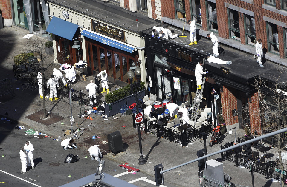 Photo - In this  Wednesday, April 17, 2013 file photo, investigators comb through the scene of one of the blast sites of the Boston Marathon explosions in Boston.  Three more suspects were taken into custody in the Boston Marathon bombing case, including two college friends of Dzhokhar Tsarnaev who came to the U.S. from Kazakhstan, officials said Wednesday May 1, 2013. (AP Photo/Julio Cortez)
