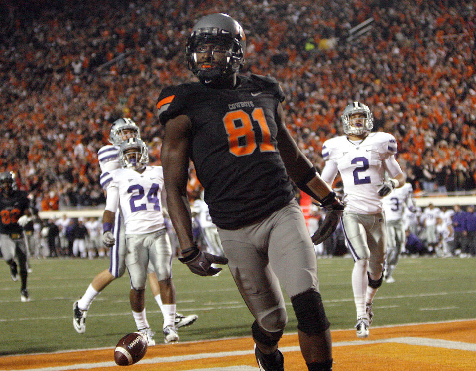 Photo - Oklahoma State's Justin Blackmon (81) celebrates a touchdown late in the fourth quarter in front of Kansas State's Nigel Malone (24) and Kansas State's Tysyn Hartman (2) during a college football game between the Oklahoma State University Cowboys (OSU) and the Kansas State University Wildcats (KSU) at Boone Pickens Stadium in Stillwater, Okla., Saturday, Nov. 5, 2011.  Photo by Sarah Phipps, The Oklahoman