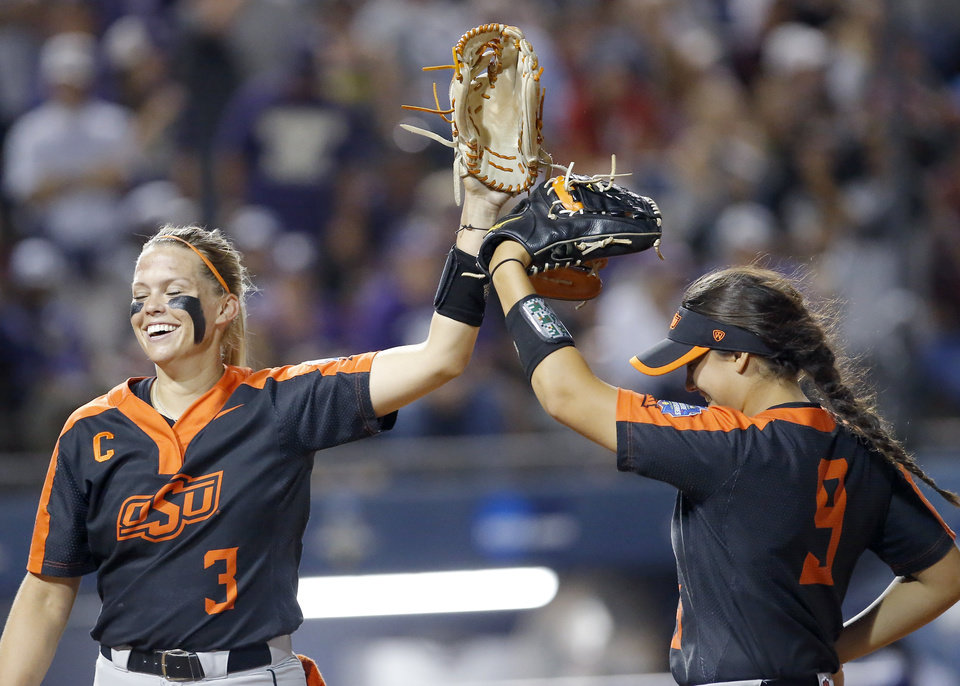 Photo - Oklahoma State's Samantha Show (3) and Chyenne Factor (9) celebrate a play in the 6th inning during a Women's College World Series between Oklahoma State (OSU) and Washington at USA Softball Hall of Fame Stadium in Oklahoma City,  Saturday, June 1, 2019. [Sarah Phipps/The Oklahoman]