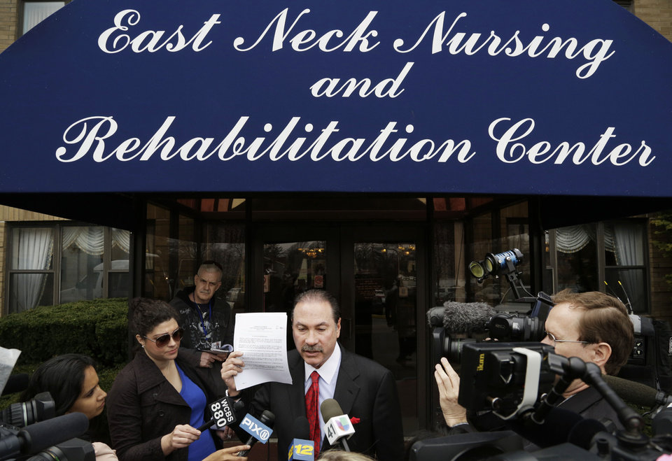 Photo - Howard Fensterman, center, representing the East Neck Nursing and Rehabilitation Center, defends the nursing home during a news conference, Tuesday, April 8, 2014, in West Babylon, N.Y. The nursing home hired a male exotic dancer to perform for its patients, according to a lawsuit filed by facility resident Bernice Youngblood in State Supreme Court in Suffolk County. (AP Photo/Mark Lennihan)