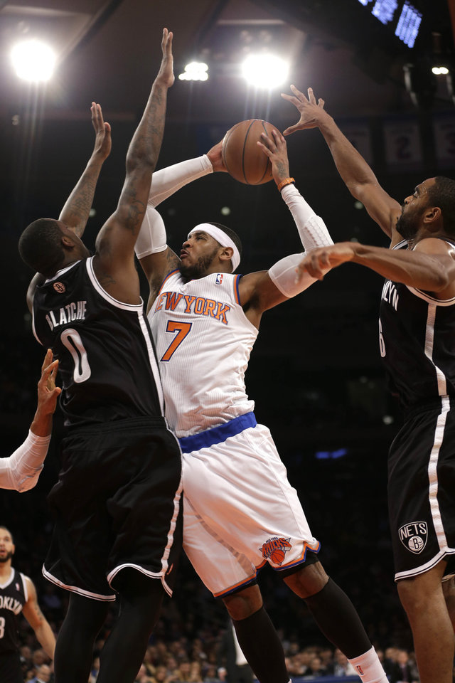 Photo - New York Knicks' Carmelo Anthony, center, is fouled by Brooklyn Nets' Andray Blatche, left, while driving to the basket past Blatche and Alan Anderson during the first half of the NBA basketball game at Madison Square Garden, Monday, Jan. 20, 2014, in New York. (AP Photo/Seth Wenig)