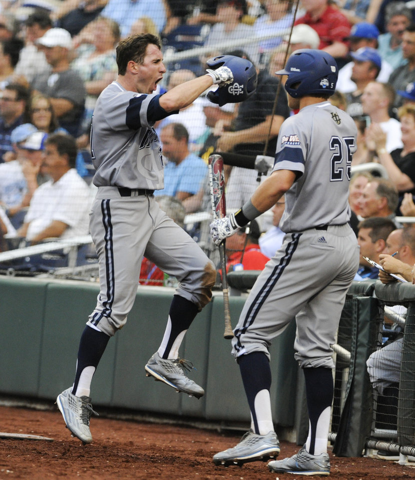 Photo - UC Irvine's Grant Palmer, left, celebrates his run against Vanderbilt in the second inning of an NCAA baseball College World Series game in Omaha, Neb., Monday, June 16, 2014. At right is UC Irvine Taylor Sparks (25). (AP Photo/Eric Francis)