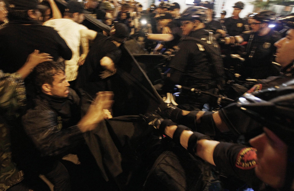 Photo - Occupy Demonstrators use a tarp to push against a police barricade during an unscheduled protest march, Tuesday, Sept. 4, 2012, in Charlotte, N.C. The Democratic National Convention begins today. (AP Photo/Gerry Broome) ORG XMIT: XDNC155
