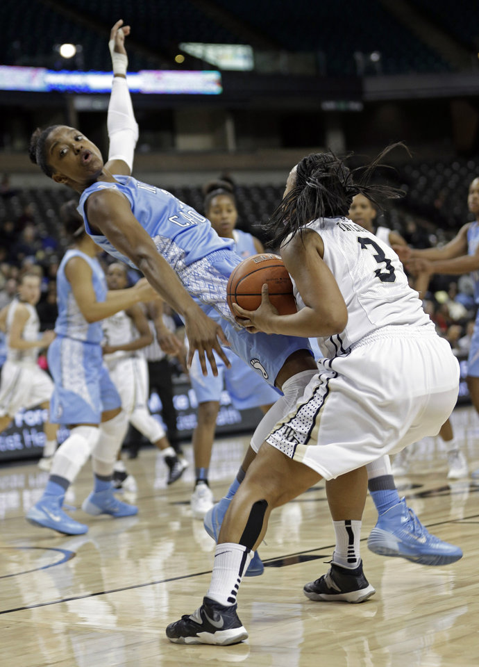 Photo - North Carolina's Diamond DeShields, left, is knocked down by Wake Forest's Ataijah Taylor, right, during the first half of an NCAA college basketball game in Winston-Salem, N.C., Thursday, Jan. 23, 2014. Taylor was charged with a foul. (AP Photo/Chuck Burton)