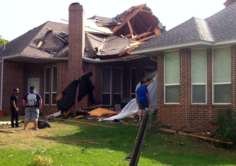 Photo - Residents of Edmond, Okla., survey storm damage from a tornado that hit their neighborhood Sunday, May 19, 2013. Forecasters had warned that the middle of the country would see severe weather throughout the weekend. (AP Photo/Sean Murphy)