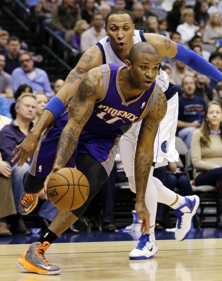 Phoenix Suns' P.J. Tucker (17) drives past Dallas Mavericks' Shawn Marion, rear, in the first half of an NBA basketball game, Sunday, Jan. 27, 2013, in Dallas. (AP Photo/Tony Gutierrez)