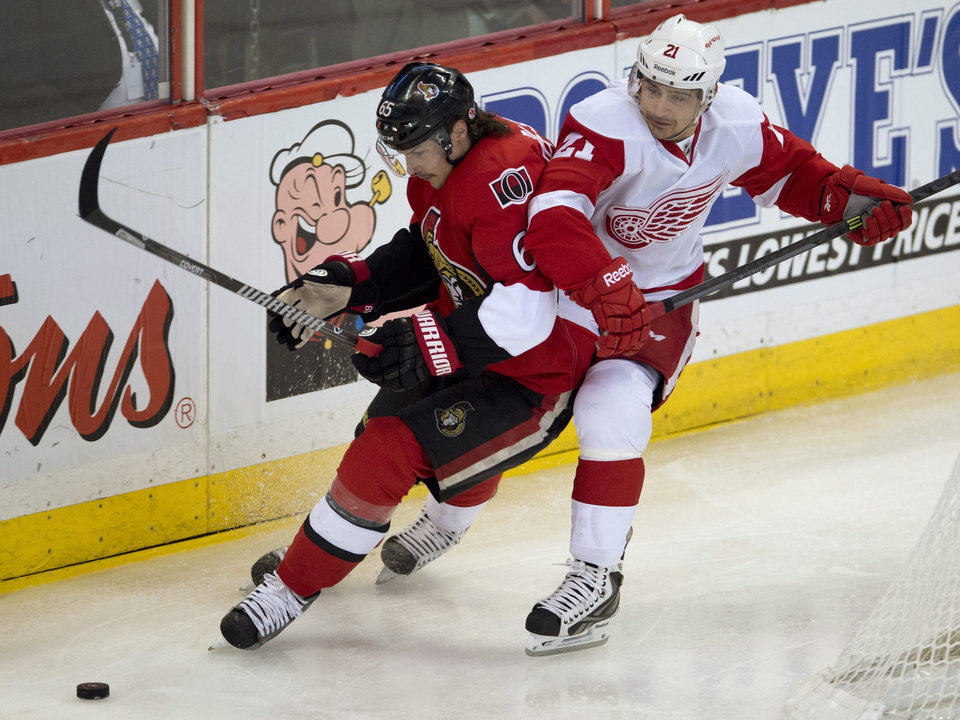 Photo - Ottawa Senators defenseman Erik Karlsson, left,  fights off Detroit Red Wings left wing Tomas Tatar behind the net during second period NHL action Sunday Dec. 1, 2013 in Ottawa, Ontario. (AP Photo/The Canadian Press, Adrian Wyld)