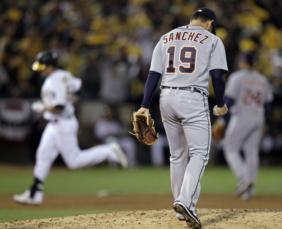 Photo -   Detroit Tigers starting pitcher Anibal Sanchez hangs his head as Oakland Athletics' Seth Smith rounds the bases on a solo home run in the fifth inning of Game 3 of an American League division baseball series in Oakland, Calif., Tuesday, Oct. 9, 2012. (AP Photo/Ben Margot)