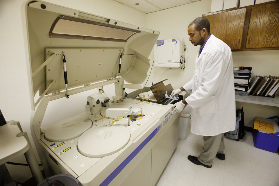 Lab technician Todd Britton loads drug testing specimens into an automated chemistry analyzer at CRG Laboratories in Oklahoma City.  Photo by Paul B. Southerland, The Oklahoman <strong>PAUL B. SOUTHERLAND - PAUL B. SOUTHERLAND</strong>