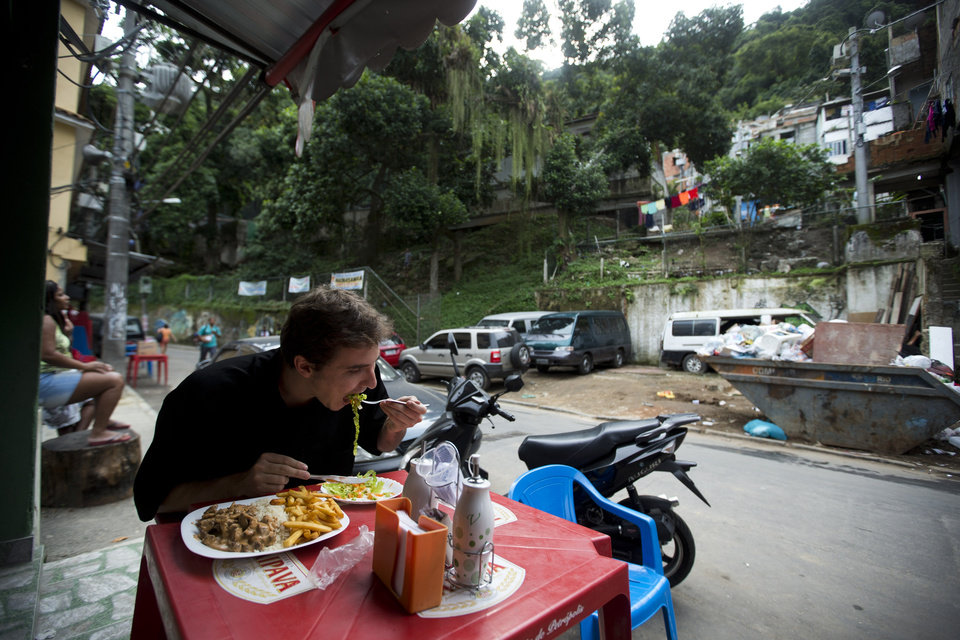 Photo - In this May 22, 2013 photo, a customer eats lunch at Restaurante 48 in Tabajaras slum, tucked into Rio's Copacabana neighborhood in Brazil. A new Portuguese-language guidebook called
