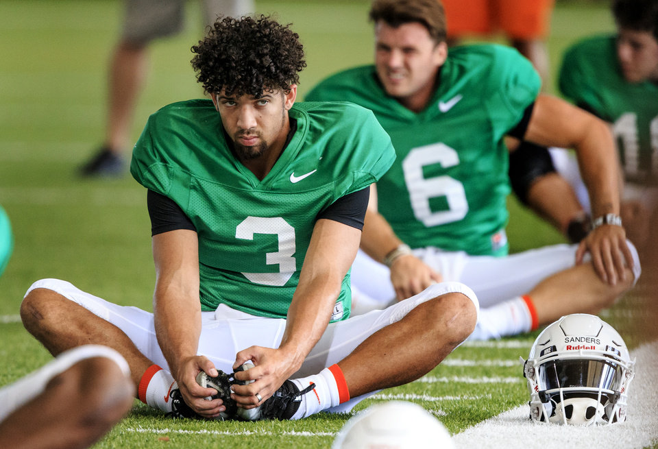 Photo - Oklahoma State University quarterbacks Spencer Sanders (3) and Dru Brown (6) stretch out at the start of OSU's team football practice at the Sherman Smith Practice Facility in Stillwater, Okla. on Tuesday, Aug. 7, 2018.    Photo by Chris Landsberger, The Oklahoman