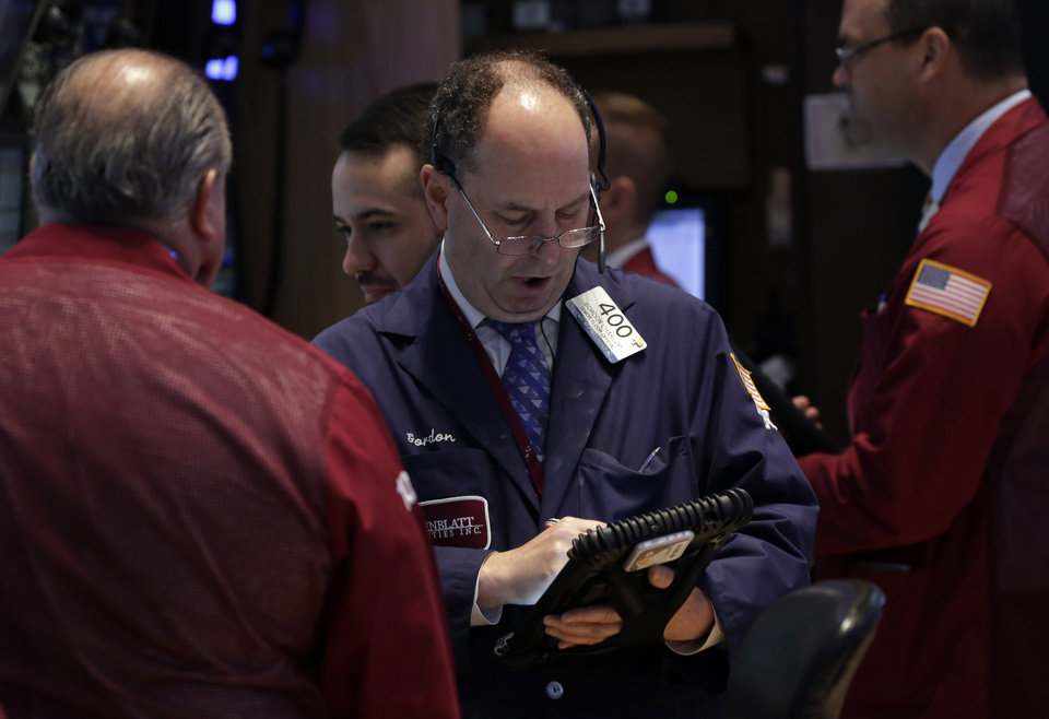 Photo - Trader Gordon Charlop, center, works on the floor of the New York Stock Exchange Monday, July 22, 2013. The stock market edged higher as a big week of earnings kicked off Monday as the results from a handful of large U.S. companies were mixed. (AP Photo/Richard Drew)