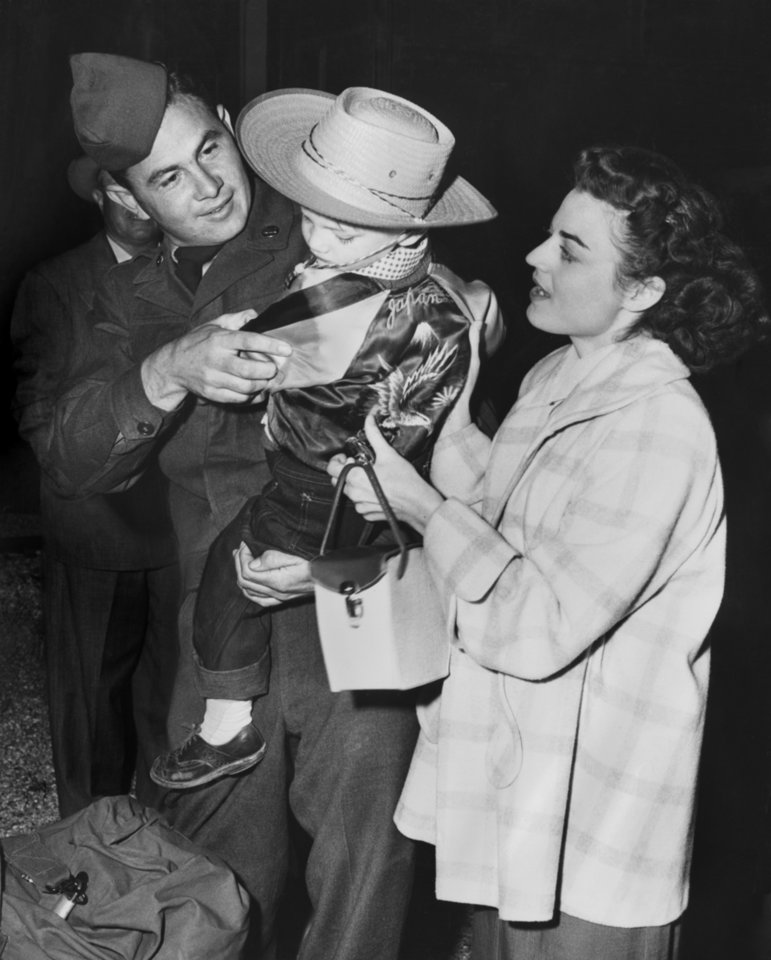 """Photo - At right, Carl Ray, 3, wore the bright satin jacket his dad Sgt. 1-C Eldon Montgomery, sent him from Japan, when he met the train Thursday morning  at Fort Sill.  (Montgomery jumped off the train at Sill, had to get back on.)  His wife, Ruth, watches with pleasure as the two get reacquainted.  The Shawnee man was the first Thunderbird off the train Thursday morning--even before the wheels stopped turning.""""  Photographer and original date unknown.  Published in The Oklahoma City Times 04/17/1952."""