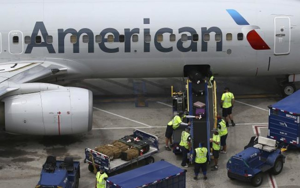 Photo -  Luggage is unloaded from an American Airlines plane at Phoenix Sky Harbor International Airport in Phoenix. [AP PHOTO]