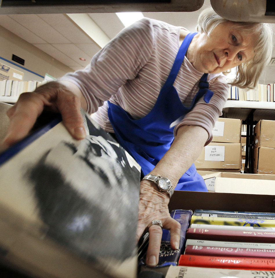 Photo - Volunteer Elizabeth Windes sorts books at the Norman Public Library on Wednesday, Oct. 17.   The Friends of the Norman Library Book Sale begins Oct. 19 for members and for the public Saturday through Monday.  Photo by Steve Sisney, The Oklahoman