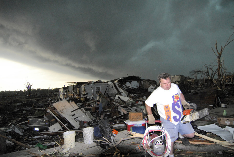 Photo - Mark Siler carries some salvageable items from the house of his friend Clay Warden as another storm approaches Joplin, Mo. on Monday, May 23, 2011. Warden's house was destroyed on Sunday by a tornado that hit the southwest Missouri town. (AP Photo/Mike Gullett) ORG XMIT: MOMG101