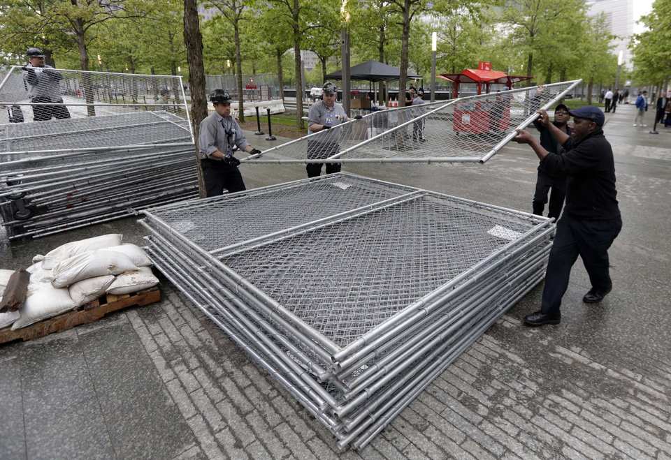 Photo - Workers on the plaza of the National September 11 Memorial & Museum stack sections of fencing removed from the venue's perimeter, in New York, Thursday, May 15, 2014. The plaza is scheduled to open to the public Thursday evening. (AP Photo/Richard Drew)
