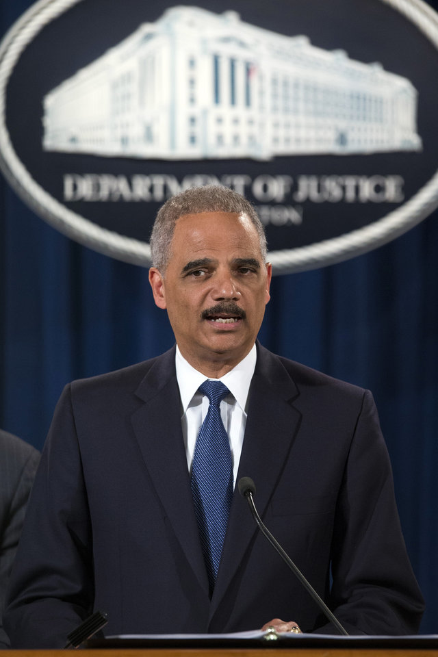 Photo - Attorney General Eric Holder speaks during a news conference at the Justice Department, on Monday, May 19, 2014, in Washington. The Justice Department on Monday charged Credit Suisse AG with helping wealthy Americans avoid paying taxes through offshore accounts, and a person familiar with the matter said the European bank has agreed to pay about $2.6 billion in penalties. (AP Photo/ Evan Vucci)