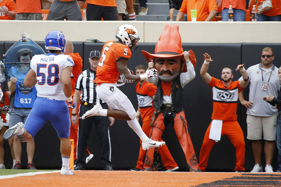 Photo - Oklahoma State's Justice Hill (5) leaps to the end zone for a touchdown during a college football game between the Oklahoma State University Cowboys (OSU) and the Boise State Broncos at Boone Pickens Stadium in Stillwater, Okla., Saturday, Sept. 15, 2018. Photo by Bryan Terry, The Oklahoman