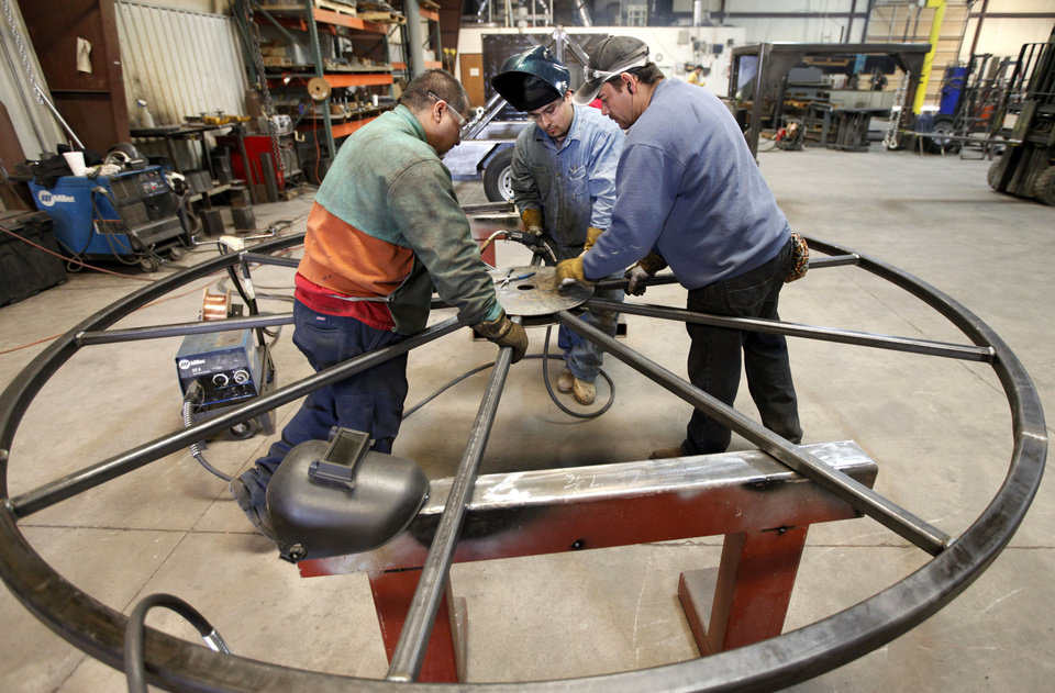 Welders piece together a metal wheel at Pro-Formance Mfg. in Oklahoma City, OK, Tuesday, February 19, 2013. The company makes spooling trailers for various industries.  By Paul Hellstern, The Oklahoman
