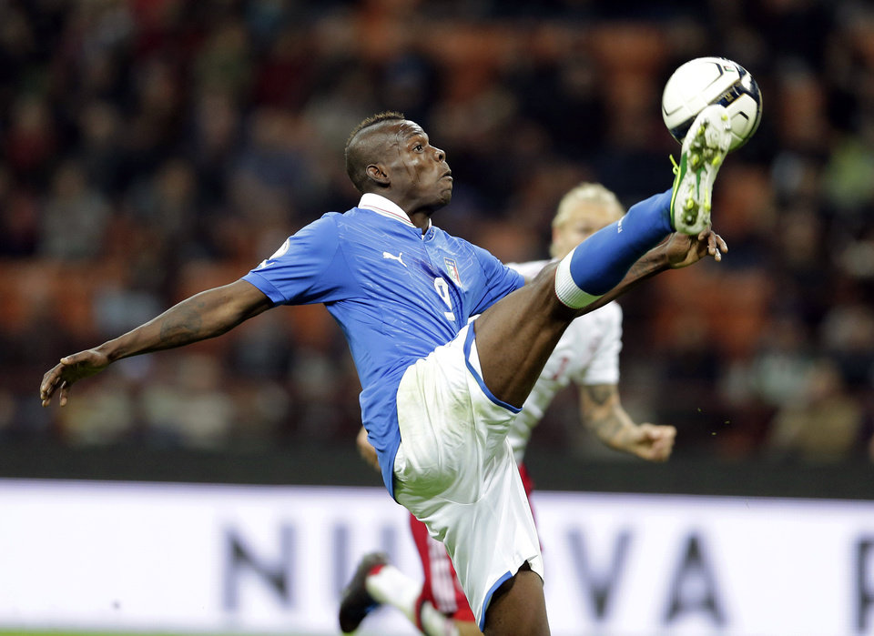 Photo -   Italy forward Mario Balotelli reaches for the ball and score his side's third goal, during the World Cup Group B qualifying soccer match at the San Siro stadium in Milan, Italy, Tuesday, Oct. 16, 2012. (AP Photo/Antonio Calanni)