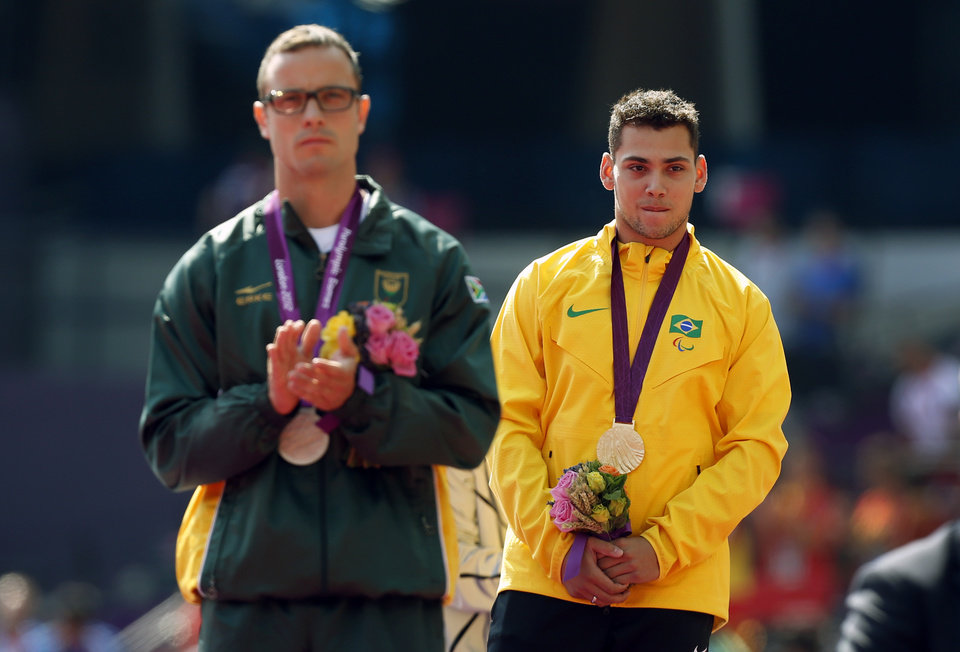 Photo -   Gold medal winner Brazil's Alan Oliveira, right, stands beside silver medalist South Africa's Oscar Pistorius after listening to his country's national anthem in the medal ceremony for the men's 200m T44 category final during the athletics competition at the 2012 Paralympics, Monday, Sept. 3, 2012, in London. Pistorius, who won a legal battle to compete wearing carbon-fiber blades alongside able-bodied runners at the Olympics last month, suggested after the race that Oliveira ran with longer prosthesis than should be allowed. (AP Photo/Matt Dunham)
