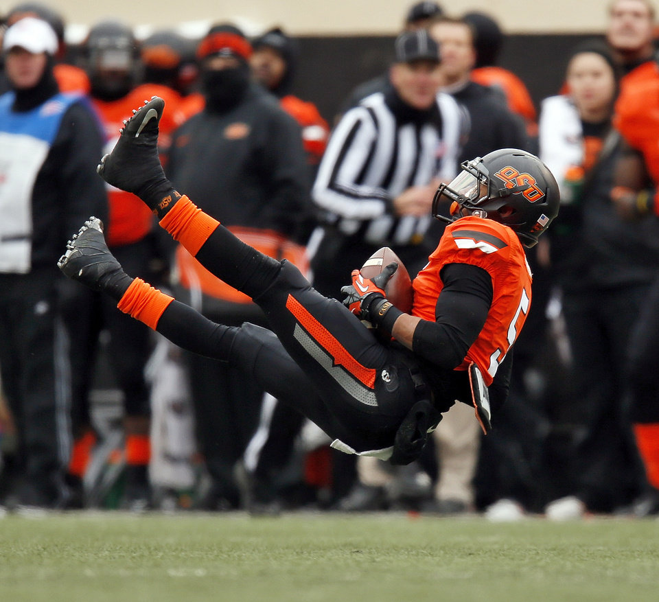 Oklahoma State's Josh Stewart (5) lands after making a catch in the third quarter during the Bedlam college football game between the Oklahoma State University Cowboys (OSU) and the University of Oklahoma Sooners (OU) at Boone Pickens Stadium in Stillwater, Okla., Saturday, Dec. 7, 2013. OU won, 33-24. Photo by Nate Billings, The Oklahoman