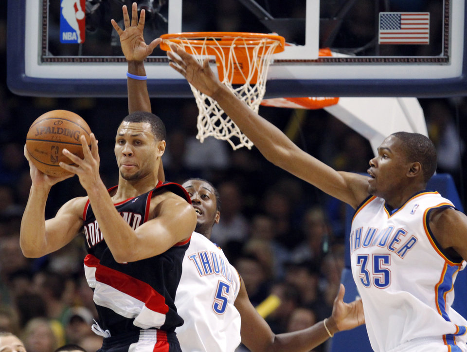 Photo - Portland's Brandon Roy (7) passes away from the defense of Oklahoma City's Kyle Weaver (5) and Kevin Durant (35) during the NBA basketball game between the Oklahoma City Thunder and the Portland Trail Blazers at the Ford Center in Oklahoma City, Friday, February 6, 2009. The Thunder won, 102-93. BY NATE BILLINGS, THE OKLAHOMAN